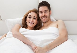 Portrait of happy young couple lying on bed together