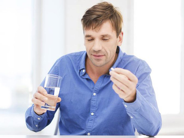 Человек пьет таблетку